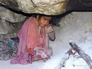 Kalika sheltering in a small cave with a small cooking fire